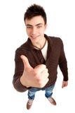 El hombre joven que muestra los pulgares sube la muestra Imagen de archivo libre de regalías