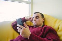 El retrato de un hombre joven que miente en una silla amarilla brillante del bolso y utiliza un teléfono móvil Reconstrucción pas Fotos de archivo