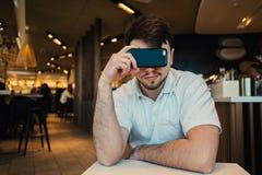 El retrato de un hombre joven que se sienta en un restaurante y cubiertas el suyo observa el teléfono móvil Imágenes de archivo libres de regalías