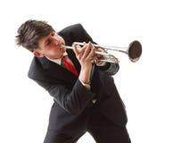 El retrato de un hombre joven que toca su trompeta juega blanco aislado Imagenes de archivo
