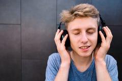 El retrato de un hombre joven sonriente con el suyo observa cerrado, disfrutando de escuchar la música en sus auriculares Fotografía de archivo