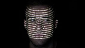 El retrato de un informático hermoso que corta los caracteres de código binario blancos se refleja en su cara - almacen de metraje de vídeo