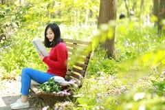 El retrato de un libro de lectura libre chino asiático de la mujer en parque del otoño de la primavera en bosque se sienta en ban Fotos de archivo libres de regalías