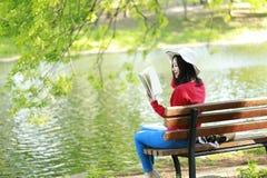 El retrato de un libro de lectura libre chino asiático de la mujer en parque del otoño de la primavera en bosque se sienta en ban Imagen de archivo
