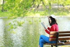 El retrato de un libro de lectura libre chino asiático de la mujer en parque del otoño de la primavera en bosque se sienta en ban Fotos de archivo