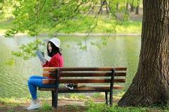El retrato de un libro de lectura libre chino asiático de la mujer en parque del otoño de la primavera en bosque se sienta en ban Imagenes de archivo