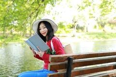 El retrato de un libro de lectura libre chino asiático de la mujer en parque del otoño de la primavera en bosque se sienta en ban Fotografía de archivo