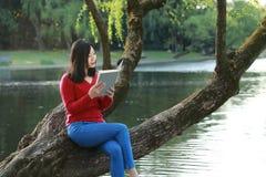 El retrato de un libro de lectura libre chino asiático de la mujer se sienta en un árbol por un río en parque del otoño de la pri Fotos de archivo