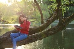 El retrato de un libro de lectura libre chino asiático de la mujer se sienta en un árbol por un río en parque del otoño de la pri Foto de archivo libre de regalías