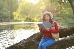 El retrato de un libro de lectura libre chino asiático de la mujer se sienta en un árbol por un río en parque del otoño de la pri Fotografía de archivo