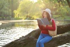 El retrato de un libro de lectura libre chino asiático de la mujer se sienta en un árbol por un río en parque del otoño de la pri Imagen de archivo