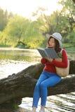 El retrato de un libro de lectura libre chino asiático de la mujer se sienta en un árbol por un río en parque del otoño de la pri Fotografía de archivo libre de regalías