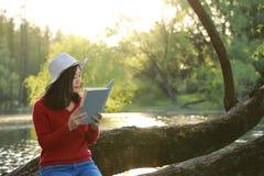 El retrato de un libro de lectura libre chino asiático de la mujer se sienta en un árbol por un río en parque del otoño de la pri Fotos de archivo libres de regalías