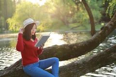 El retrato de un libro de lectura libre chino asiático de la mujer se sienta en un árbol por un río en parque del otoño de la pri Imágenes de archivo libres de regalías