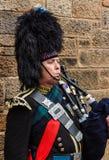 El retrato de un militar vistió al gaitero que tocaba la gaita Imagen de archivo libre de regalías