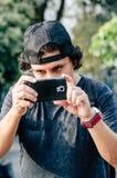 El retrato de un muchacho adolescente atractivo que sostiene su smartphone con su mano y toma la fotografía Imagen de archivo