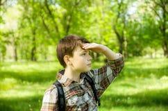 El retrato de un muchacho en un verde empañó el fondo Al aire libre, verano Imagen de archivo libre de regalías