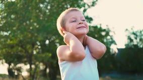 El retrato de un niño activo alegre, el niño da vuelta a sus manos detrás de su cabeza almacen de metraje de vídeo