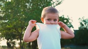 El retrato de un niño activo alegre, niño tímido oculta la parte de la cara debajo de una camiseta blanca metrajes