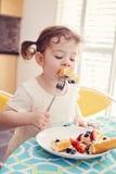 El retrato de un niño caucásico blanco feliz de la muchacha del niño con las coletas en el vestido blanco que come el desayuno se Fotografía de archivo libre de regalías