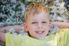 El retrato de un niño pequeño que está mintiendo en la hierba cubrió con Fotografía de archivo libre de regalías