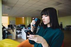 El retrato de un oficinista joven, hermoso de la mujer que beba la taza negra del café y utiliza un teléfono móvil Rotura en el t Foto de archivo libre de regalías