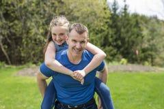 El retrato de un padre que lleva a la muchacha adolescente encendido apoya en el parque Imagenes de archivo