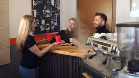 El retrato de un par en una cafetería detrás de la barra, Barista le da el café almacen de metraje de vídeo