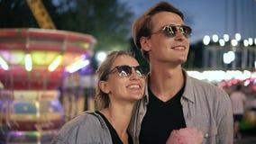 El retrato de un par joven, alegre del inconformista en gafas de sol está mirando la luz de las atracciones Gente joven feliz, so almacen de video