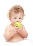 El retrato de un pelo rizado del niño come un аpple verde Foto de archivo libre de regalías