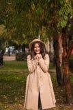 El retrato de un sombrero que lleva de la muchacha y la capa en otoño parquean imagen de archivo libre de regalías