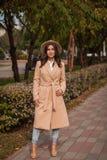 El retrato de un sombrero que lleva de la muchacha y la capa en otoño parquean Fotos de archivo