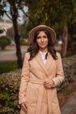 El retrato de un sombrero que lleva de la muchacha y la capa en otoño parquean foto de archivo