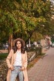 El retrato de un sombrero que lleva de la muchacha y la capa en otoño parquean Fotos de archivo libres de regalías