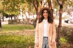 El retrato de un sombrero que lleva de la muchacha y la capa en otoño parquean fotografía de archivo libre de regalías