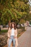 El retrato de un sombrero que lleva de la muchacha y la capa en otoño parquean Foto de archivo libre de regalías