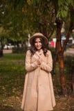 El retrato de un sombrero que lleva de la muchacha y la capa en otoño parquean Imagen de archivo