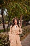 El retrato de un sombrero que lleva de la muchacha y la capa en otoño parquean Imagenes de archivo