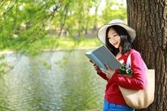 El retrato de una belleza china asiática está sonriendo y el libro de lectura se sienta en un árbol por un río en parque del otoñ Foto de archivo