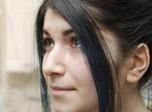 El retrato de una chica joven con el pelo negro y el marrón observa Imagen de archivo libre de regalías