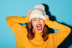 El retrato de una chica joven feliz se vistió en sombrero del invierno Fotos de archivo