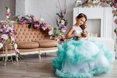 El retrato de una chica joven hermosa con los ojos azules, compone y peinado en vestido enorme de la turquesa con el terrier de Y Fotos de archivo