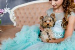 El retrato de una chica joven hermosa con los ojos azules, compone y peinado en vestido enorme de la turquesa con el terrier de Y Fotografía de archivo