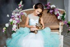 El retrato de una chica joven hermosa con los ojos azules, compone y peinado en vestido enorme de la turquesa con el terrier de Y Imagen de archivo libre de regalías