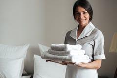 El retrato de una criada del hotel que se considera fresca limpia las toallas dobladas imagen de archivo libre de regalías