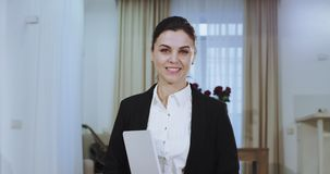 El retrato de una empresaria sonriente en un traje casual que mira derecho a la cámara, tiene una sonrisa blanca grande y metrajes