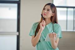 El retrato de una enfermera sonriente hermosa Thinking que muestra el espacio en blanco es Foto de archivo libre de regalías