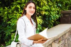 El retrato de una estudiante universitaria sonriente está sosteniendo el libro Imagen de archivo libre de regalías