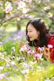 El retrato de una flor china asiática del olor de la mujer de la naturaleza y escucha la música en un parque de la primavera disf Fotografía de archivo