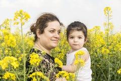El retrato de una madre feliz joven abrazó a su niña en el campo del canola imagenes de archivo